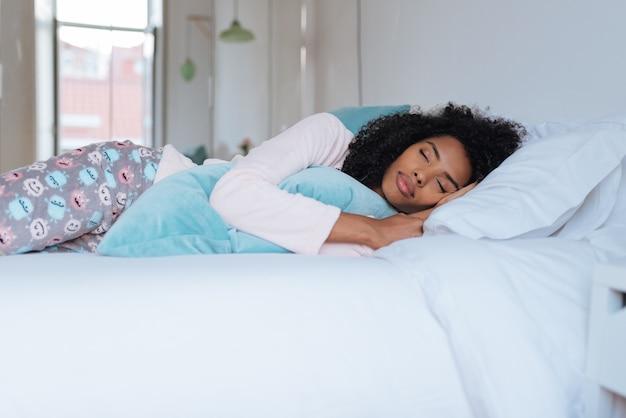 Счастливая красивая молодая чернокожая женщина лежа в кровати спать