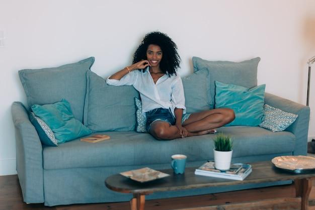 Красивая черная молодая женщина, сидения на диване