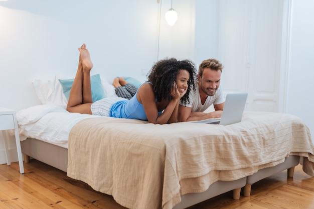 幸せな若いカップルが自宅のコンピューターでベッドに横たわってリラックス