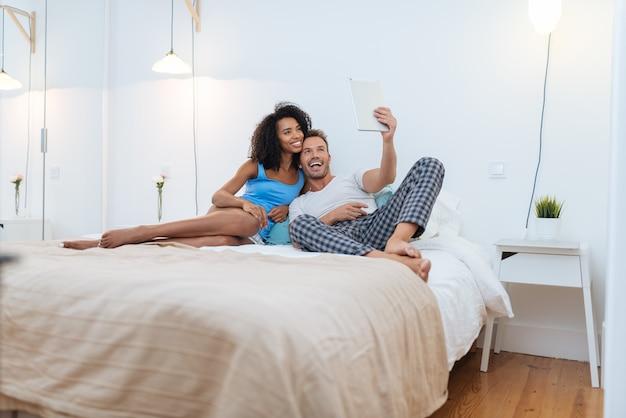 Счастливая молодая пара отдыхает дома лежа в постели на планшете, принимая селфи