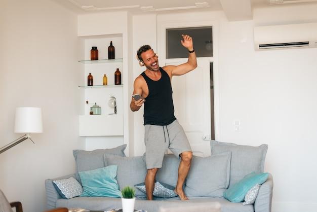 音楽を聴くと踊りの携帯電話で自宅でソファに立っている幸せな若い金髪男