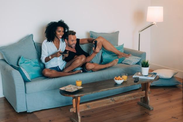 Счастливая молодая пара отдыхает дома на диване, развлекаясь, играя в видеоигры