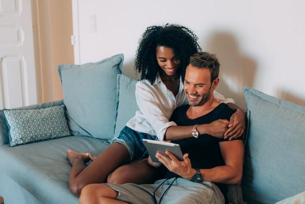幸せな若いカップルは、タブレットでソファに座って自宅でリラックス