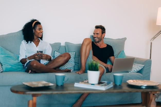 幸せな若いカップルは、音楽を聴く携帯電話とコンピューターのソファで自宅でリラックス