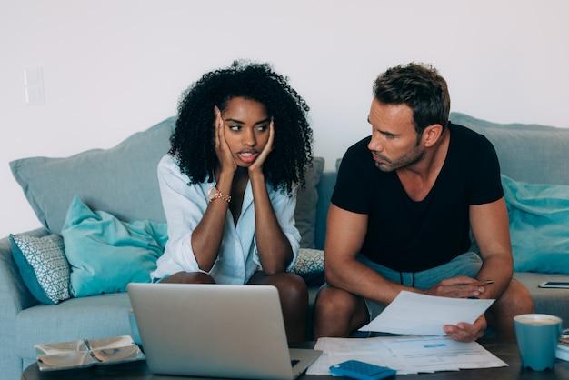 ソファで若い異人種間のカップルは、紙の仕事で計算を行う金融問題で強調しました。