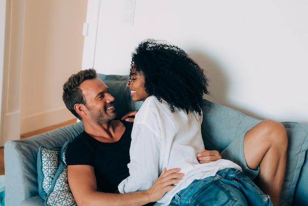 幸せな若いカップルがお互いに遊んで楽しんでソファで自宅でリラックス