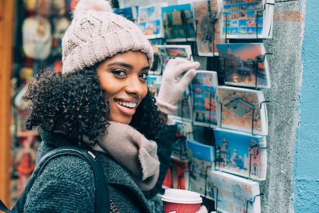 冬にマドリードの街をさまようコーヒーを飲む若い黒人女性