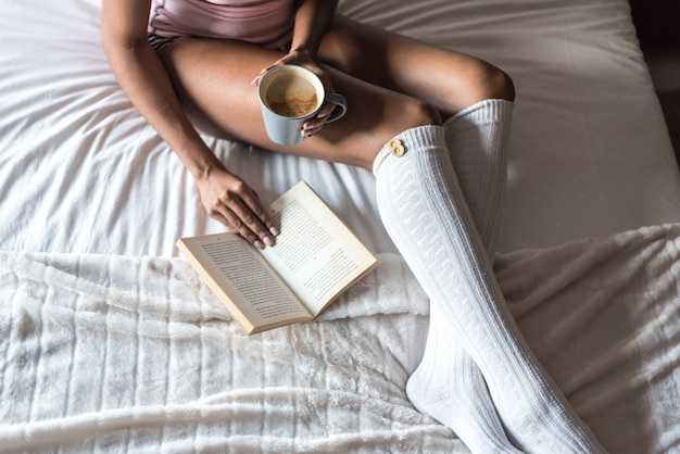 Чернокожая женщина читает книгу и пьет кофе на кровати с носками