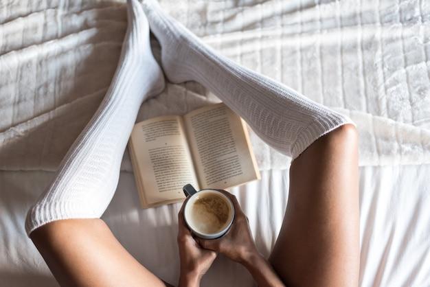 Женщина читает книгу и пьет кофе на кровати с носками