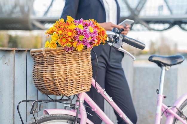Бизнес черная женщина, стоя у своего старинного велосипеда, выступая на мобильном телефоне