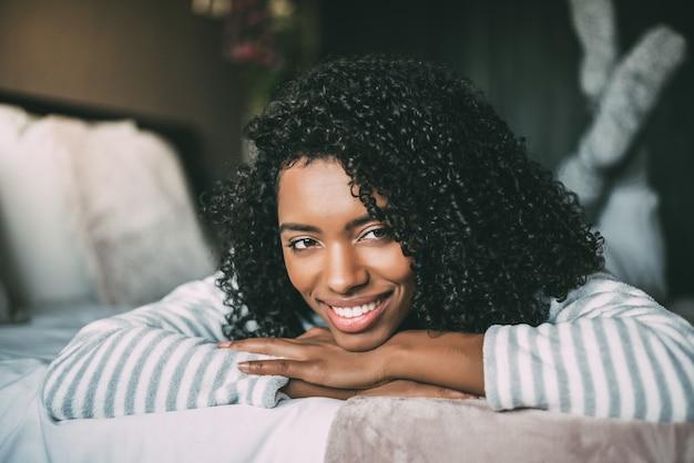Крупным планом довольно черная женщина с вьющимися волосами, улыбаясь и лежа на кровати, глядя