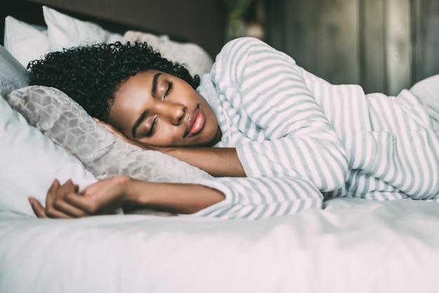 目を閉じてベッドで寝ている巻き毛のかなり黒人女性のクローズアップ