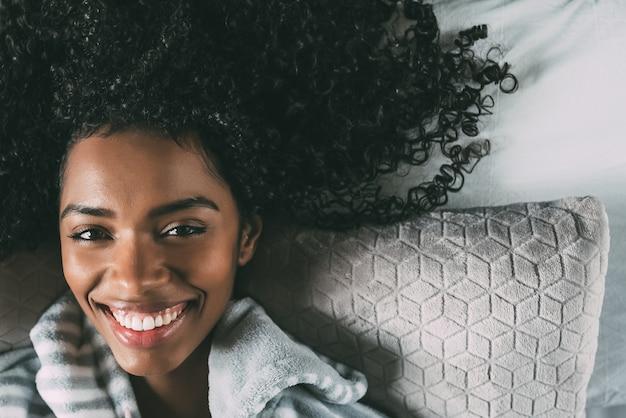 Красивая черная женщина с вьющимися волосами, улыбаясь и лежа на кровати, глядя на камеру