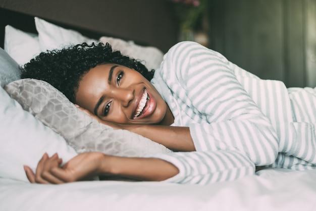 Крупным планом довольно черная женщина с вьющимися волосами, улыбаясь и лежа на кровати, глядя на камеру