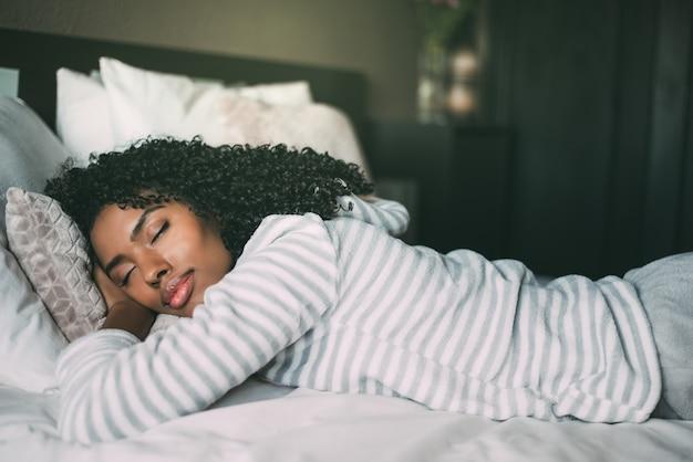 Крупным планом довольно черная женщина с вьющимися волосами, спать в постели с закрытыми глазами