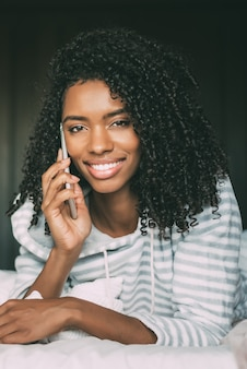 カメラを見てベッドの上のスマートフォンで巻き毛のかなり黒人女性のクローズアップ