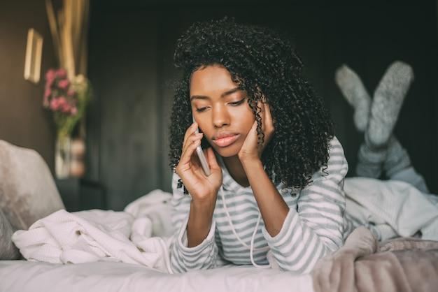 ベッドでスマートフォンを使用して巻き毛を持つ美しい深刻な思慮深く、悲しい黒人女性