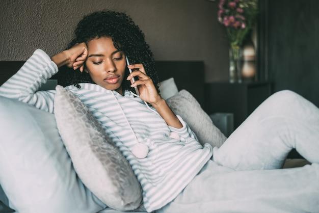 Красивая серьезная вдумчивая и грустная негритянка с вьющимися волосами, используя смартфон на кровати