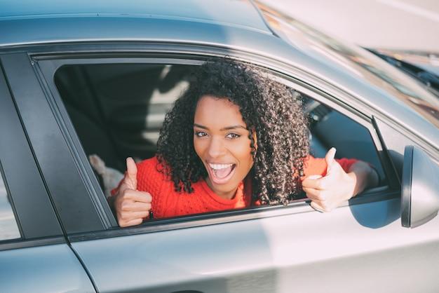 Молодая негритянка сидит в машине улыбается
