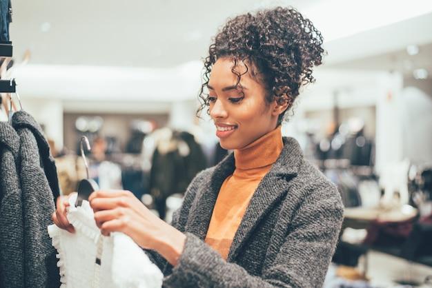 Черная молодая женщина, делать покупки в магазине