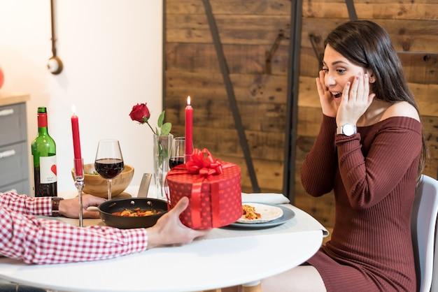 Молодая счастливая пара празднует день святого валентина с ужином у себя дома пить вино, ура.