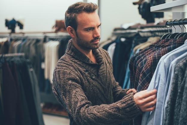 Молодой белокурый человек делает покупки в магазине