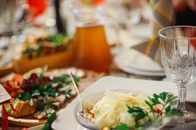 Картофельное пюре с орехами на тарелке в ресторане. холодные закуски в ресторане на банкете в честь праздника. новогодний стол в украине.