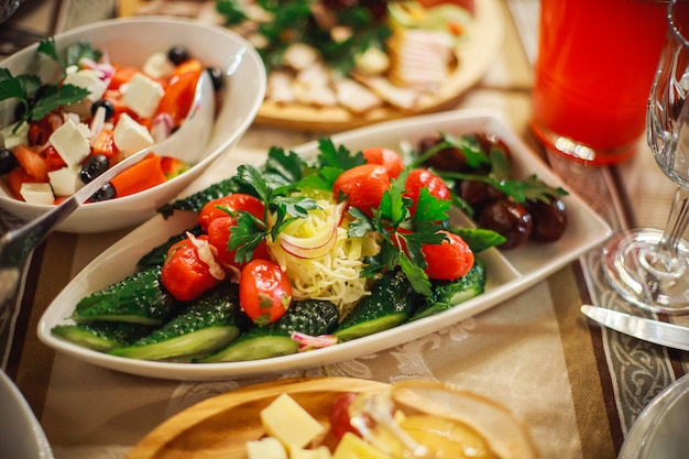 Тарелка с солеными огурцами - соленые, соленые помидоры, соленые огурцы, соленый лук и заправленные петрушкой. холодные закуски в ресторане на банкете в честь праздника.