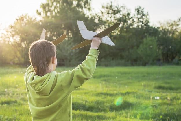 子供はおもちゃの飛行機を起動します。空の旅。少年は日没でフィールドを渡って村を歩きます。