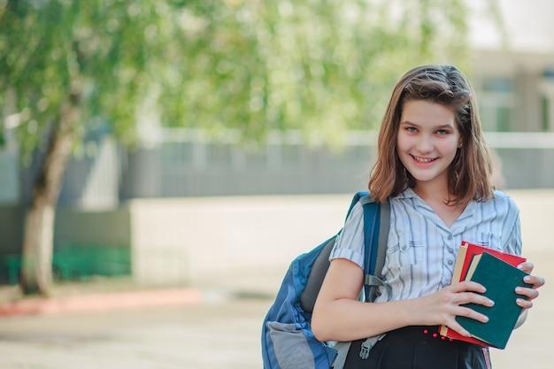 Девушка держит две книги красный и зеленый и улыбается