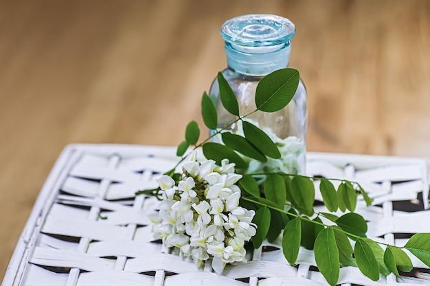薬の瓶の近くの白い花アカシアの束。季節のハーブのコレクション。ニセアカシア、ニセアカシア、偽アカシアの枝。薬用植物からの薬。