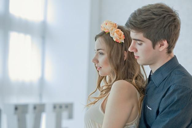 男は女の子を後ろから抱擁します。晴れた日に光の大きな窓に対する愛のカップル。