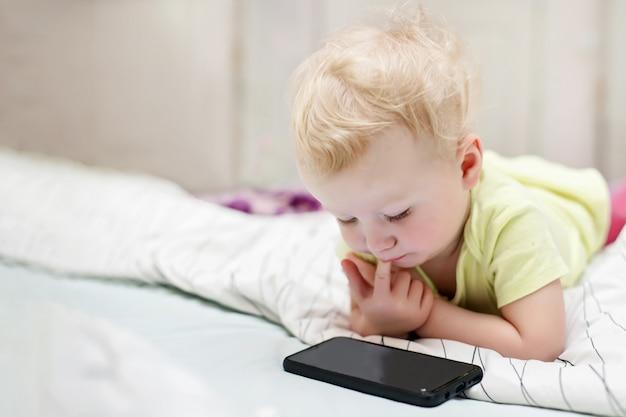 小さな子供はベッドに横になっている携帯電話で漫画を見る。スマートフォンを使用して自宅で遊ぶ女の子。