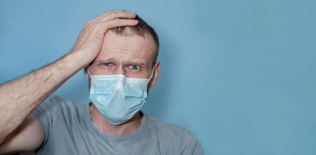 男は恐怖で頭を抱えた。医療用保護マスクの病人。コロナウイルスの患者の間でインフルエンザまたは風邪がウイルスから保護されている