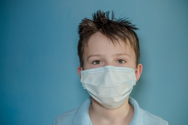 水色の壁に医療マスクの少年。コロナウイルス患者のインフルエンザの子供