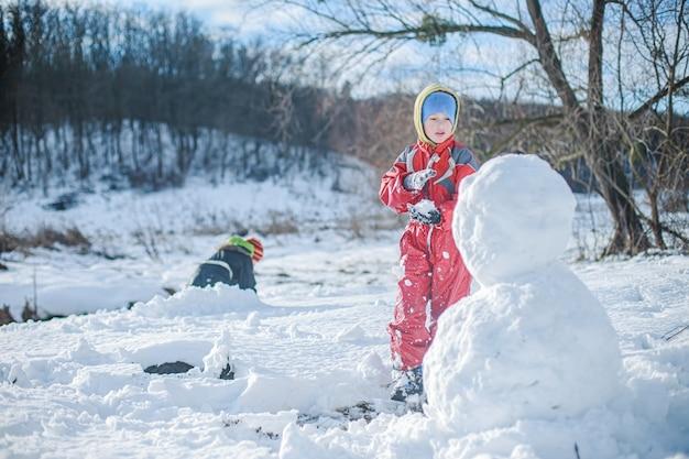 Мальчик в красном комбинезоне строит снеговика из снега