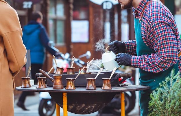 男は路上でコーヒーをれます。