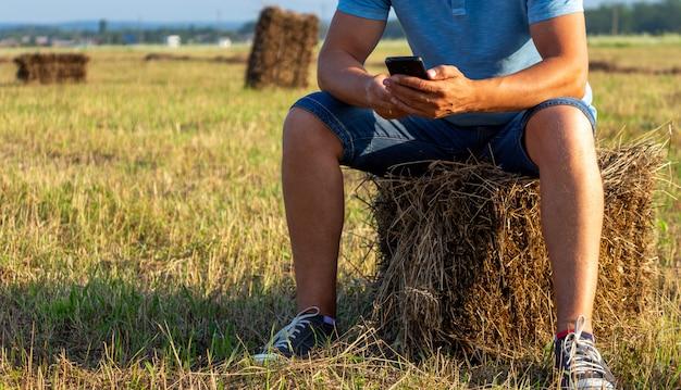 Фермер сидит в поле с телефоном на стоге сена. в поле с телефоном на стоге сена.