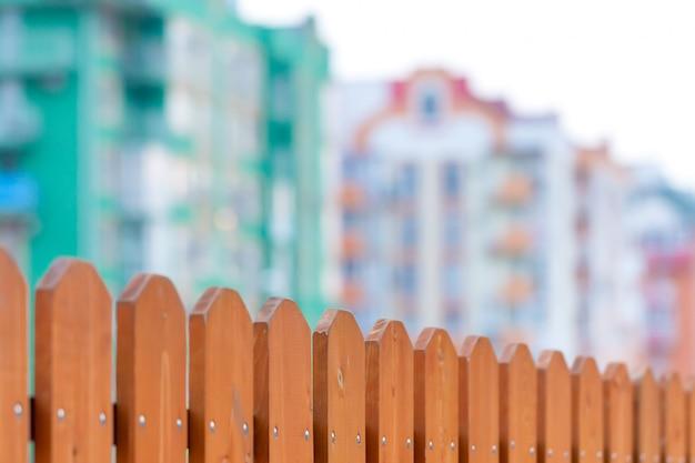 手前には板で作られたフェンスがあり、奥にはぼやけたアパートの建物があります。