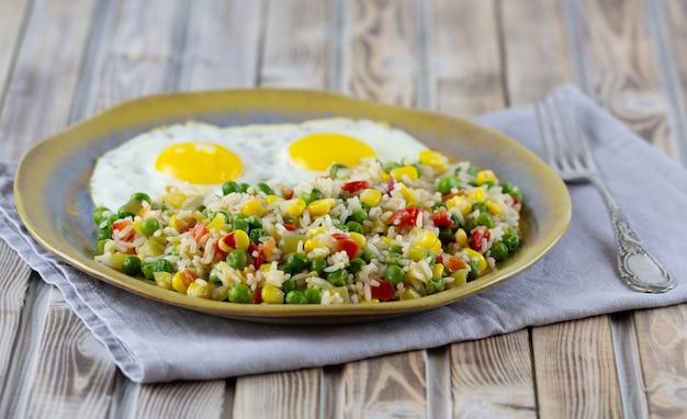 Рис с овощами перец, горох, кукуруза и яичница на тарелке