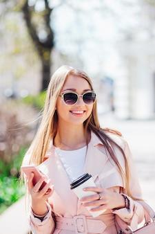 上流階級の女性。屋外でファッショナブルな女性のテキストメッセージ。サングラスとコーヒーとピンクのジャケットのファッション女性