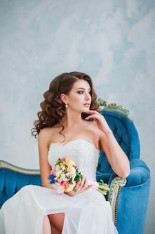ウェディングドレスの魅力的な若い女性。屋内の花束を持つ花嫁