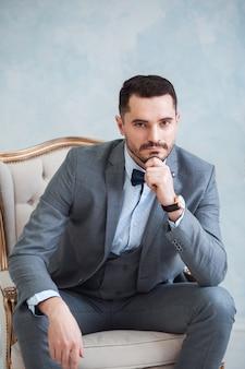 グレーのスーツでハンサムな成人男性の肖像画。新郎は花嫁を待っています。結婚式