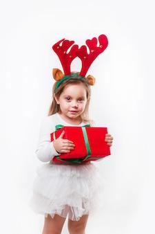 クリスマスの赤いプレゼントボックスを保持している鹿の角の小さな赤ちゃん