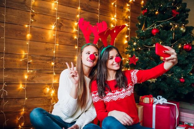 Улыбающиеся подруги, делающие селфи со смартфоном. новогоднее настроение