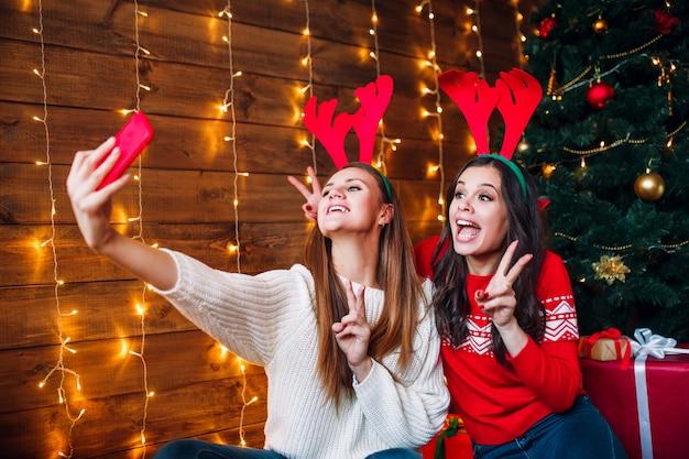 Две лучшие подружки принимают селфи в спальне возле елки