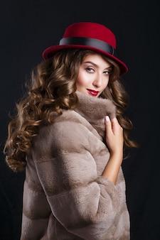 Гламурный портрет красивой модели женщины с красными губами и длинными темными волосами в роскошной шубе и шляпе цвета марсала
