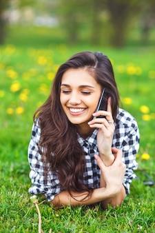 公園でスマートフォンで入力する美しい女性の肖像画