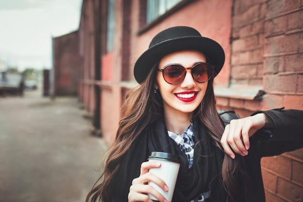サングラスと帽子屋外でトレンディな女性。通りで一杯のコーヒーを保持しているサングラスの若い女性