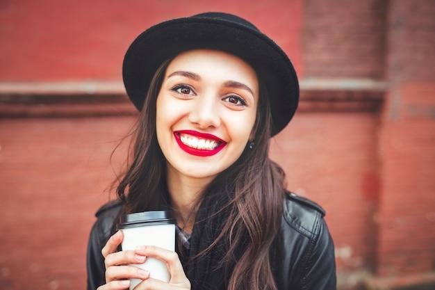 屋外の飲み物と帽子でトレンディな女性。通りと一杯のコーヒーを保持している赤い唇を持つ若い女性